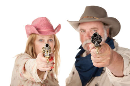 Couple in western wear pointing pistols with serious faces photo
