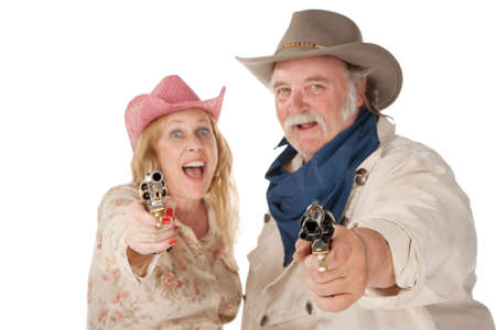 Couple in western wear pointing pistols and laughing