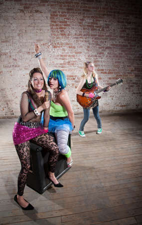 Young all girl punk rock band performs in a warehouse photo