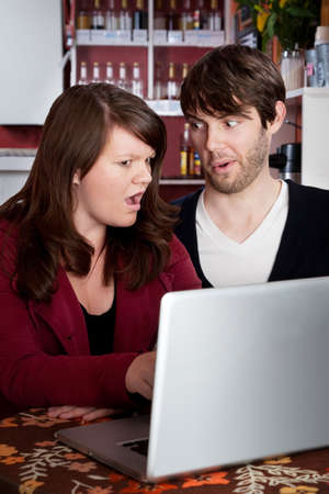 disbelief: Woman and man staring in disbelief at a laptop Stock Photo