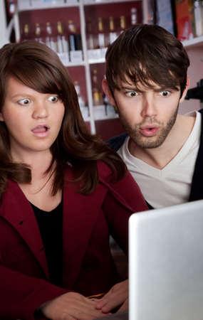 pornografia: Mujer y hombre mirando fijamente en incredulidad en un ordenador port�til