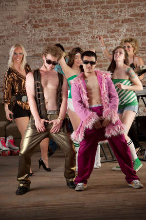 defiant: Raunchy dancing men with sunglasses at a 1970s Disco Music Party Stock Photo