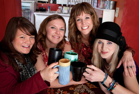 Four young happy female friends at a cafe photo