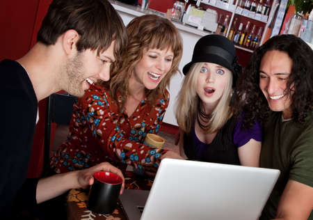 inappropriate: Four friends laughing at a video on a laptop