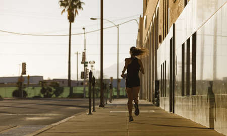 Woman running down a city block in the morning. photo