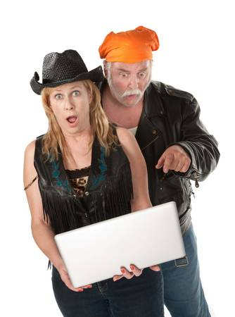 Biker couple surprised about something on a laptop photo
