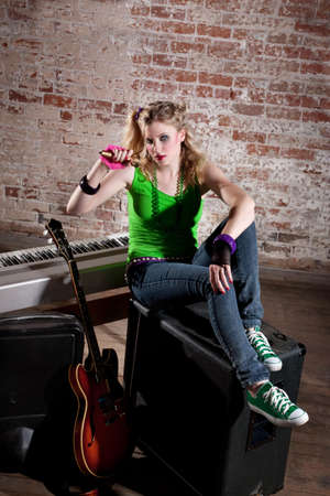 Young punk rocker girl with blond hair practices singing photo