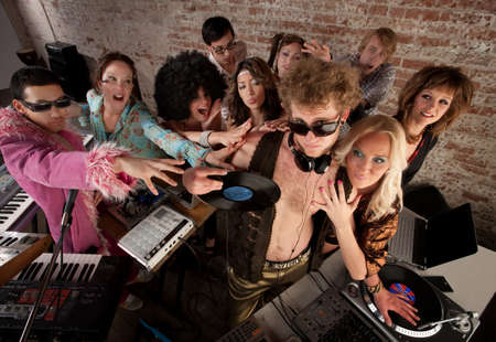 Famous DJ crowded by fans and requests at a party photo