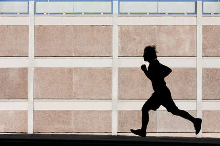 shadow: Man in the shadows of building runs for exercise.