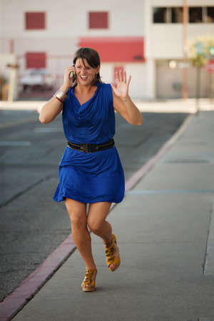 harried: Woman runs down the street while having a cell phone conversation.