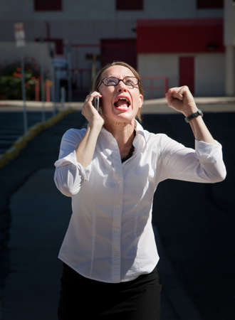 harried: Terribly upset young woman screams into cell phone Stock Photo