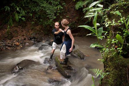 Woman helping man cross ruching Costa Rican river