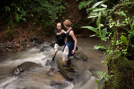 help: Woman helping man cross ruching Costa Rican river