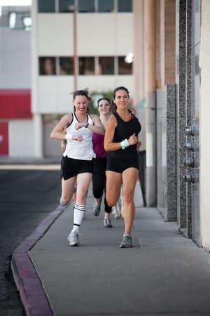 mujeres corriendo: Grupo de mujeres de carreras hacia abajo de una calle para la diversi�n de la ciudad.  Foto de archivo