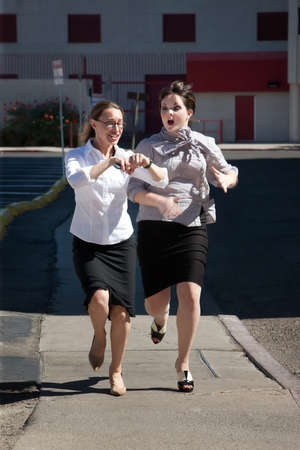 running late: Two women are late for work and running.