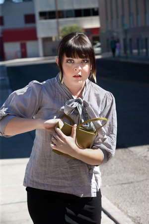 Young woman frantically searches purse on city block.