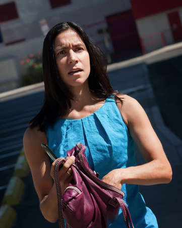 harried: Woman, standing looking confused on city street. Stock Photo