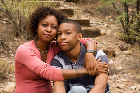 Loving single-mother hugging her handsome teenage son photo