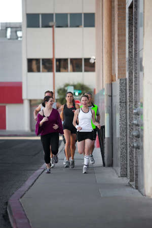 sidewalk talk: Men and women running for exercise downtown Stock Photo