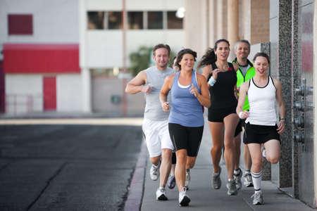 男性と女性運動ダウンタウンを実行しています。