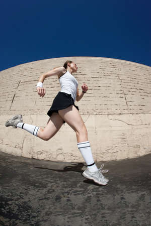 Woman runner practices sprinting towards the fiish line. photo