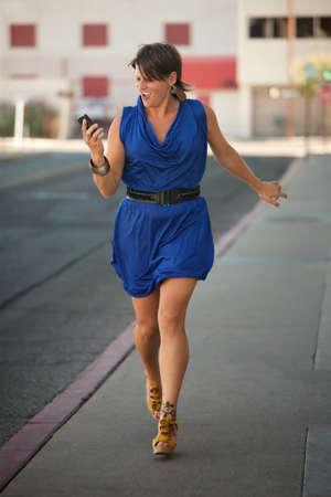 sidewalk talk: Woman walks down the street while making a phone call