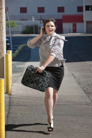running late: Woman is running down street late for meeting.