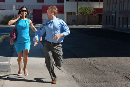 harried: Man and woman run down street to catch taxi.