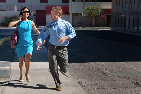 run down: Man and woman run down street to catch taxi.