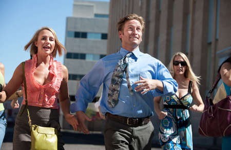 harried: Man races ahead of women in the city.