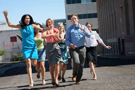 Happy men and women running down the street. photo