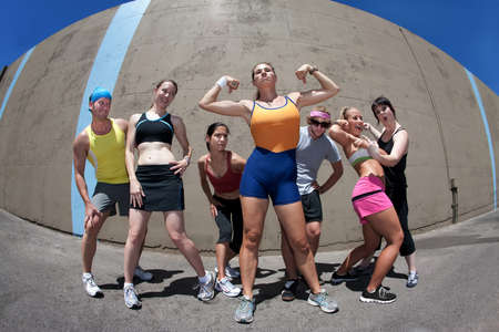 tricep: Pretty female runner poses and flexes with friends