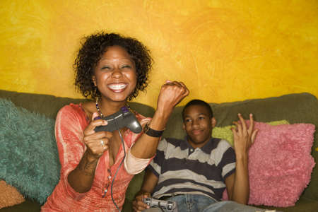 Good-looking mom and son Playing a Video Game with Handheld Controllers photo