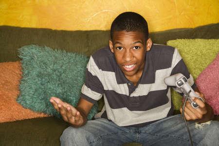 beroofd: Knappe jonge man speelt een video spel met handheld-controllers  Stockfoto