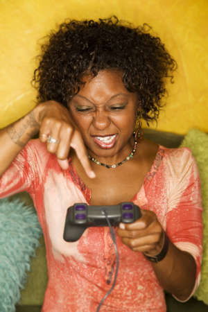 Attractive woman plays video game with hand held controllers photo
