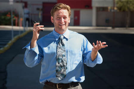 harried: Exasperated business man with cell phone outdoors Stock Photo