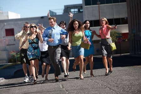cel: Gruppo di duro lavoro gli uomini di affari e donne correre gi� la strada cittadina.