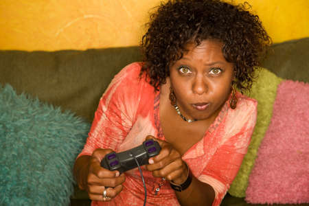 Attractive woman plays video game with hand held controller photo