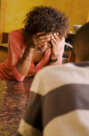 Distraught African-American woman and male talking in kitchen