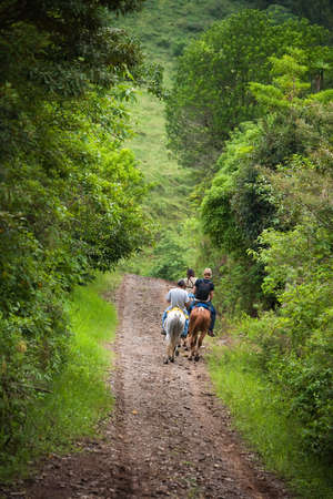 costa rican: Tourists on horseback in Costa Rican cloud forest Stock Photo