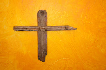symbols: Rugged wooden cross hanging on yellow wall