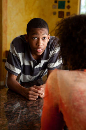Surprised young African-American man talking to woman in kitchen photo