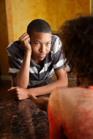 conversaciones: apuesto adolescente estadounidense habla con mujer en cocina  Foto de archivo