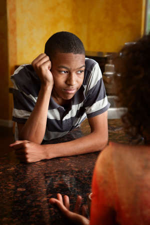 Upset African-American young man and woman talking in kitchen Stock Photo