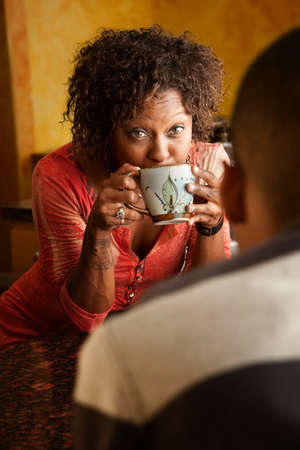 Attractive African-American woman talks with male in kitchen photo