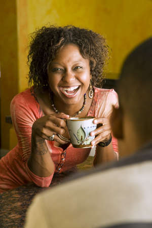 Pretty African-American woman talks to male in kitchen photo