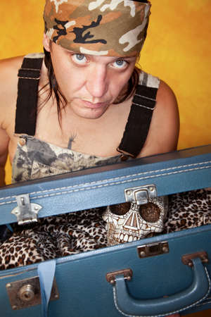 Native American man with ornate skull in a suitcase photo