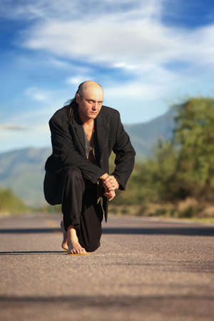 barefoot cowboy: Strange indigenous man in the middle of a road Stock Photo