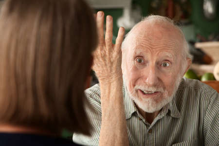 Senior couple at home in kitchen focusing on angry man photo