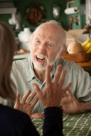 focusing: Senior couple at home in kitchen focusing on angry man